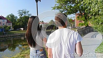 Cerca de la vista trasera de una bonita pareja joven que camina por el parque. rear. outdoor. Tiro medio almacen de video
