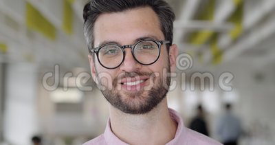 Cerca de un hombre alegre y guapo mirando a la cámara y sonriendo Trabajador de oficina varón con barba de buen humor almacen de metraje de vídeo