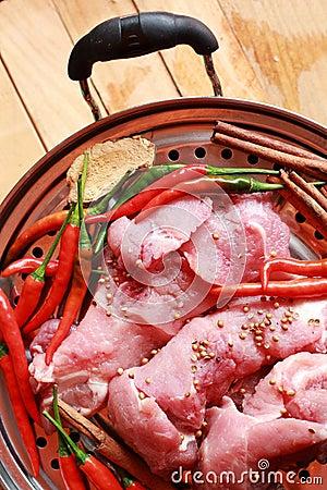 Cerdo crudo en tabla de cortar y verduras
