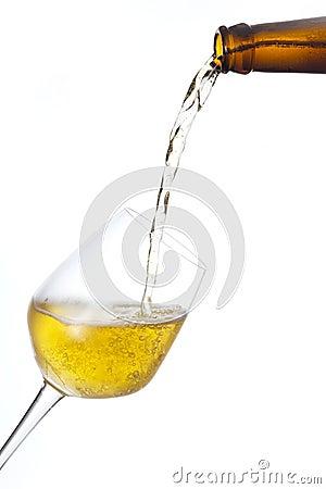 A cerveja derrama dentro um vidro.