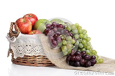 Cesta por completo de manzanas y de uvas jugosas