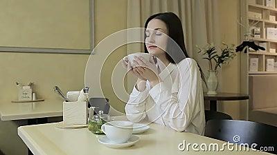 Chá bebendo da jovem mulher em um café video estoque