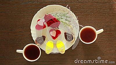 Chá preto em umas canecas lunch tabela com uma bebida e uma sobremesa Vista de acima vídeos de arquivo