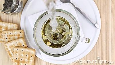 Chá verde de folha com jasmim é feito com água fervente Bebida quente em copo transparente de vidro Café da manhã leve e saudável video estoque