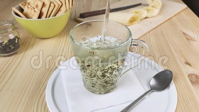 Chá verde de folha com jasmim é feito com água fervente Bebida quente em copo transparente de vidro Café da manhã saudável, video estoque