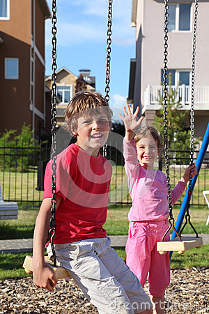 Chłopiec siedzi na huśtawce i dziewczyna macha jej rękę