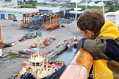 Chłopiec target605_0_ w szkockiej kraty spojrzeniu przy portem