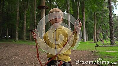 Chłopiec w lasowym przygoda parku pokazuje jego zbawczą nicielnicę Plenerowy rozrywki centrum z wspinaczkowymi aktywność zbiory