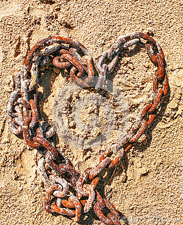 Chain in the shape of a heart on the sand