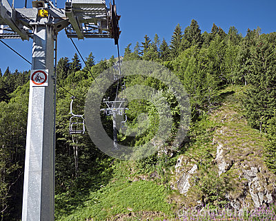 Chair lift up wooded mountains in summer