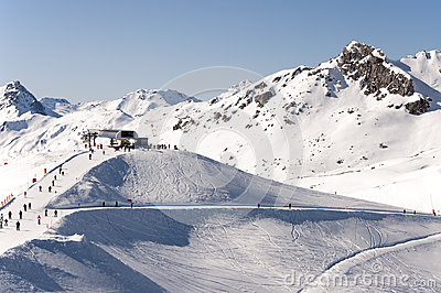 Chairlift station, skiers and ski piste in Alps