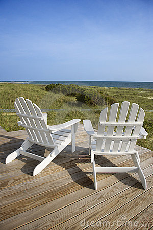 Chairs sitting on a wooden deck facing the shore the grassy beach