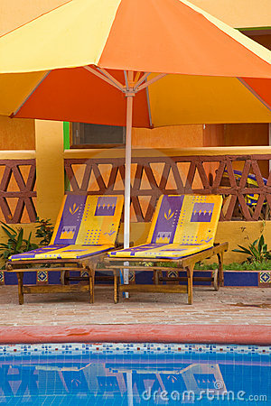 Chairs Under A Poolside Umbrella