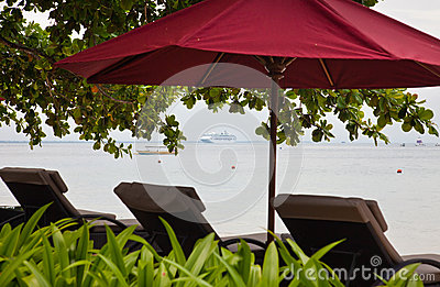 Chaise lounges and umbrella on an ocean coast.
