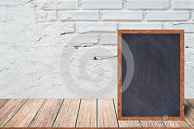 Chalkboard wood frame, blackboard sign menu on wooden table and with brick background. Stock Photo