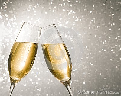 Champagne flutes with golden bubbles on silver light bokeh background