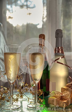 Champagne in glasses, gift box and sunbeam