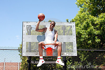 Champion basketball player sitting in hoop