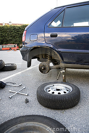 Changing car tires at parking lot