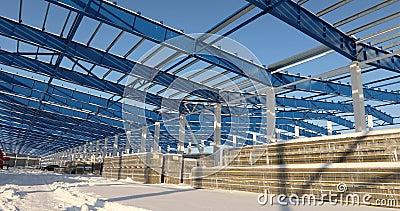 Chantier de construction moderne d'entrepôt, la structure d'acier de construction d'un nouveau bâtiment commercial contre un bleu banque de vidéos