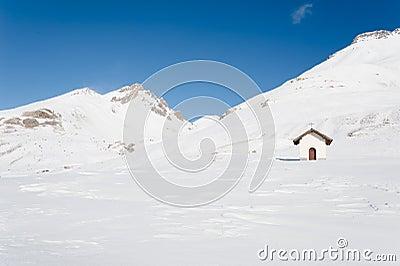 Chapel among snowy mountains