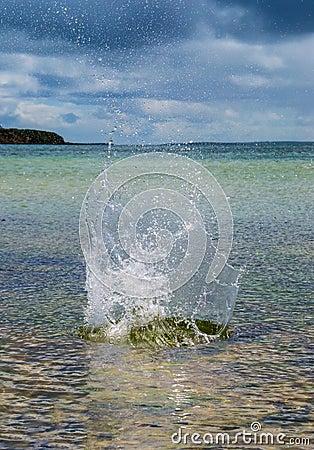 Chapoteo grande en el agua con el mar prístino en el fondo
