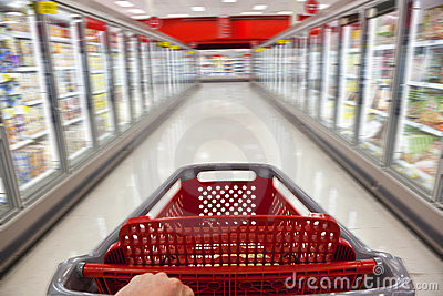 Chariot à achats de tache floue de mouvement dans le supermarché