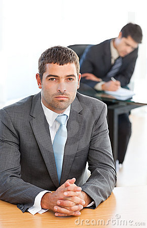 Charismatic businessman sitting in the foreground