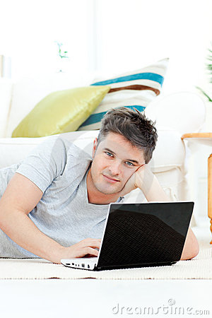 Charismatic young man using his laptop at home