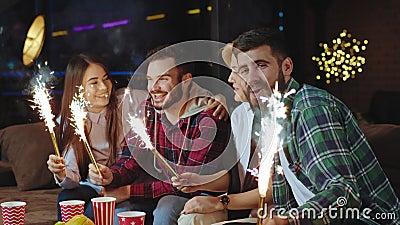 Charismatisch attraktive Freunde vor der Kamera, die einige Funkeln verwenden und etwas feiern, während sie auf der Kamera sitzen stock video