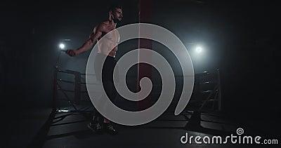 Charismatische atletische man in een donkere kruisfitnessklasse met een naakt lichaam dat over het touw springt waar hij zweet va stock videobeelden