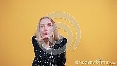 Charmant jeune femme caucasienne soufflant, baiser d'air de sable sur un mur orange isolé clips vidéos
