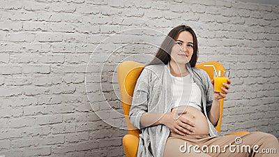 Charmerend jong zwanger meisje wat betreft het naakte glas van de buikholding met het verfrissen van vitaminejus d'orange stock video