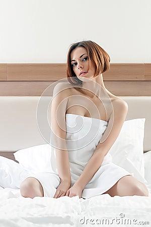 Charmig kvinna med kort hår som poserar efter dusch