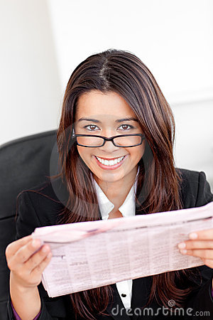 Charming asian businesswoman holding a newspaper