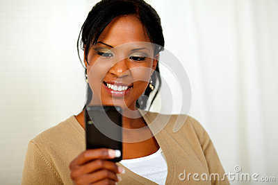 Charming black woman sending message by cellphone