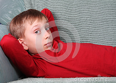 Blond Caucasian boy in red lying on green sofa looking into the camera surprised