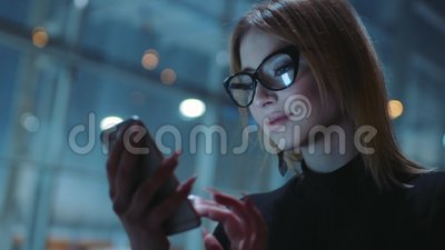 Charming blonde in a good mood in the glasses with black rim and dark clothes is on the evening street. She is near the. Business center. The girl is stock video footage