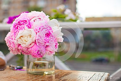 Charming bouquet of peonies in vase on table at