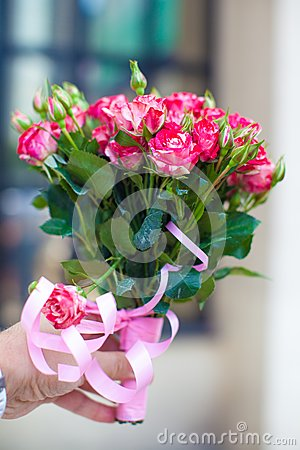 Charming bouquet of roses in woman s hand