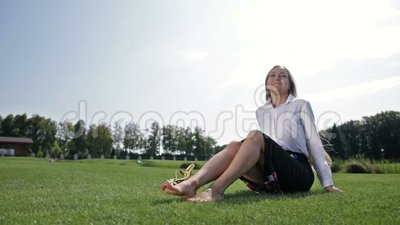 Charming businesswoman relaxing on the green grass stock footage