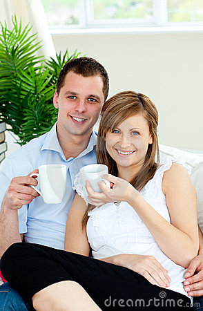 Charming couple holding cups of coffee smiling