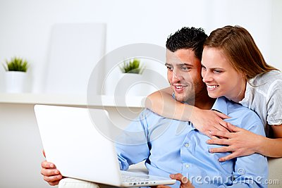 Charming couple using laptop together