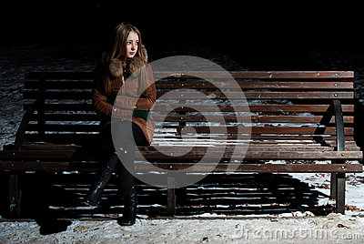 Charming girl in expectation on a bench
