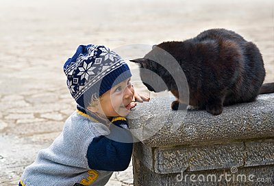 Charming little boy playing with a black cat