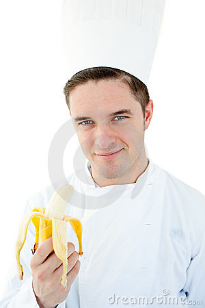 Charming male cook holding a banana and smiling