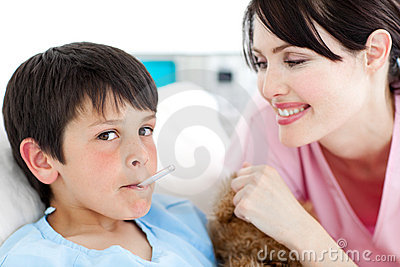 Charming nurse taking little boy s temperature