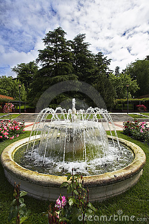 Charming round fountain in a garden of roses