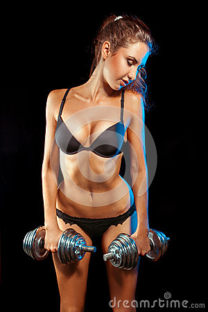 Charming sports woman in black lingerie with dumbbells