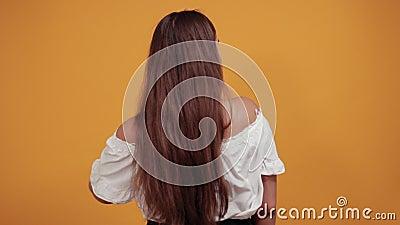 Charming, ung kvinna som visar brunette, lång frisyr och pekar finger lager videofilmer